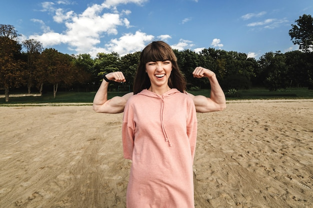 Desportiva mulher atlética energético usa sorrisos de top rosa esportes
