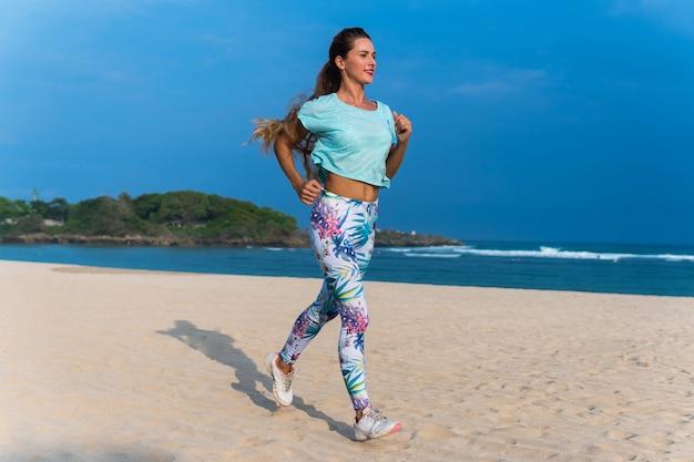 Desportiva mulher correndo na praia