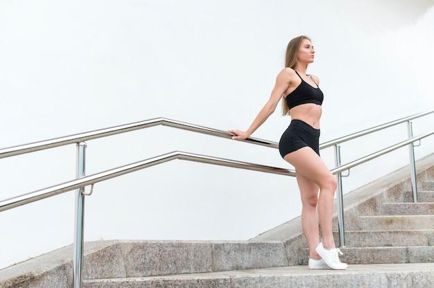 Desportiva mulher descansando e olhando para longe