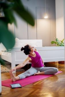 Desportiva mulher envelhecida média fazendo exercícios de ioga com alongamento de pernas