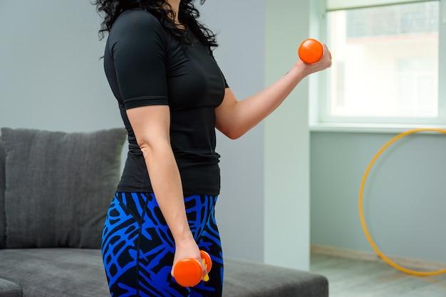 Desportiva mulher exercitando em casa. treinamento feminino com halteres. conceito de esporte e recreação.