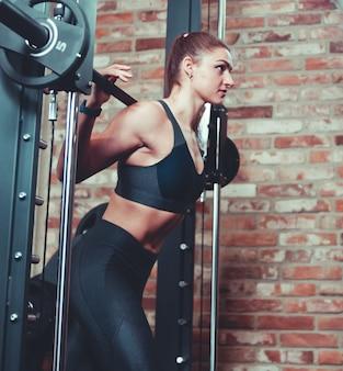 Desportiva mulher fazendo estocada exercício no smith rack bar contra a parede de tijolos