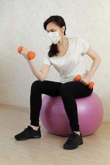 Desportiva mulher fazendo exercício com bola de fitness em casa