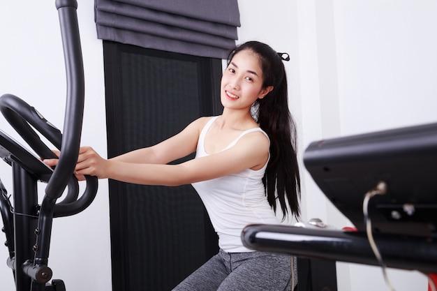Desportiva mulher fazendo exercícios com instrutor elíptico