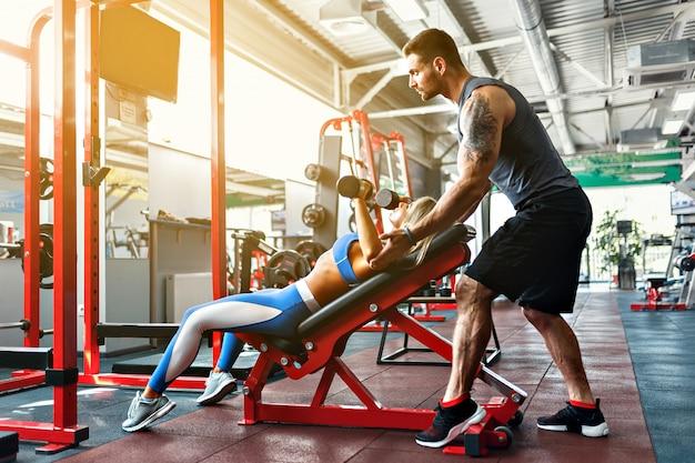 Desportiva mulher fazendo exercícios de peso com a ajuda de seu personal trainer na academia