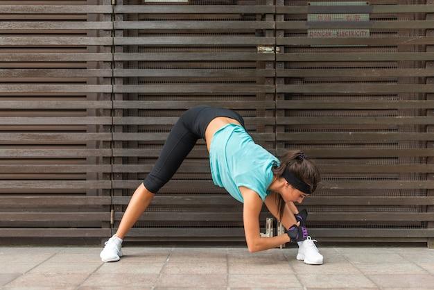 Desportiva mulher jovem e bonita praticando ioga fazendo pose de dobrar para a frente de pernas largas, exercícios de alongamento