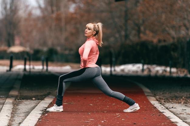 Desportiva mulher loira caucasiana fazendo pulmões na pista. comprimento total, vista lateral.