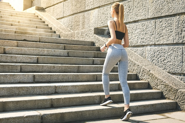 Desportiva mulher malhando subindo escadas ao ar livre para treino de manhã