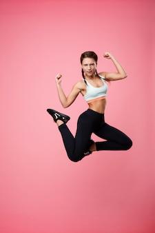 Desportiva mulher pulando fazendo poses olhando diretamente rosa