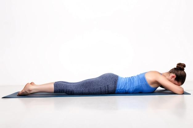Desportiva mulher relaxa no yoga asana makarasana