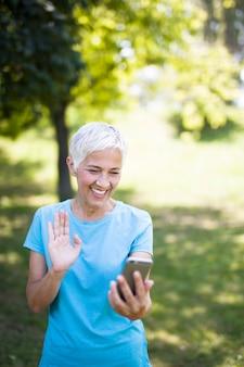 Desportiva mulher sênior usando telefone celular no parque