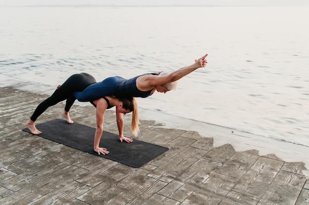 Desportivas mulheres posando em acro yoga asana ao ar livre perto do mar
