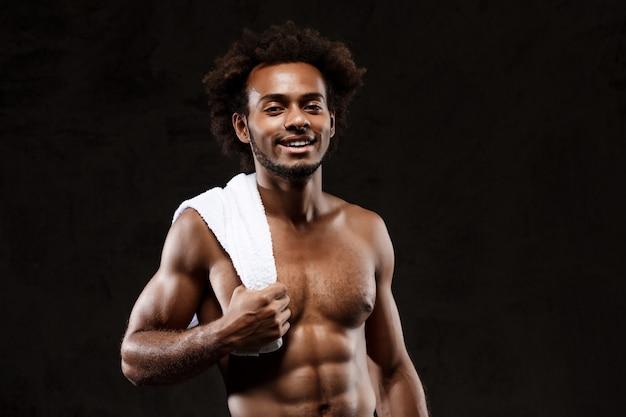 Desportivo africano jovem posando sobre parede preta.