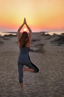 Desportivo cabe mulher fazendo hatha yoga asana vrikshasana árvore pose na praia tropical no pôr do sol