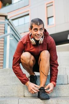 Desportivo homem amarrar sapatos em ambiente urbano
