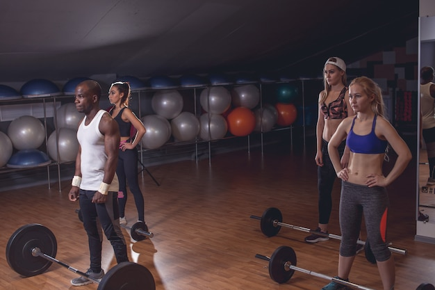 Desportivo homem e mulher se preparando para fazer exercício com halteres. horizontal tiro dentro de casa
