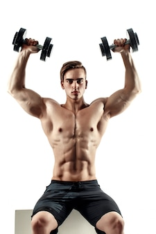 Desportivo homem em formação, bombeando os músculos das costas e mãos com halteres.