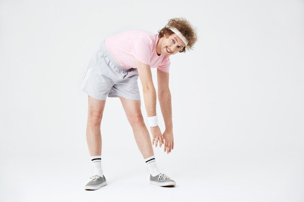 Desportivo homem esticando os músculos das costas e pernas