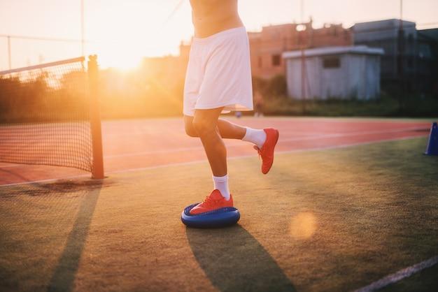 Desportivo homem fazendo exercícios de equilíbrio lá fora. feche de sua perna na bola.