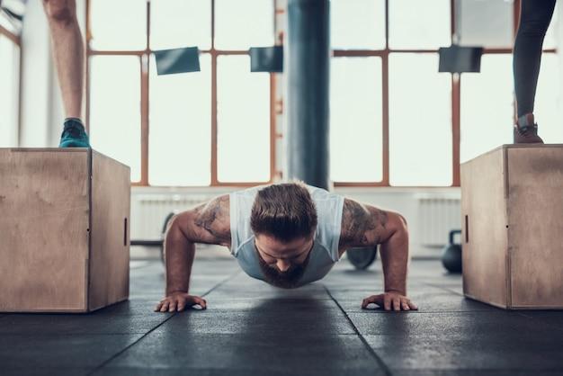 Desportivo homem fazendo push ups entre dois atletas.