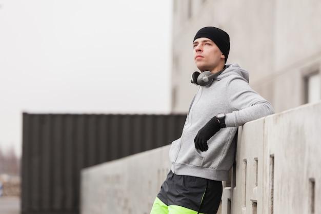 Desportivo, homem, inclinar-se, contra, parede