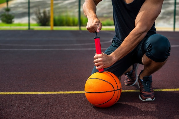 Desportivo homem inflar uma bola