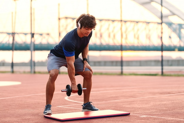 Desportivo homem musculoso com cabelo encaracolado, levantando halteres em pé na quadra de manhã. fones de ouvido nas orelhas.