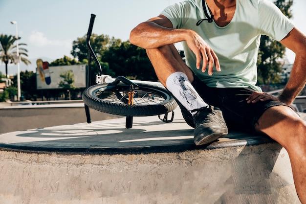 Desportivo homem parado perto de uma bicicleta de bmx