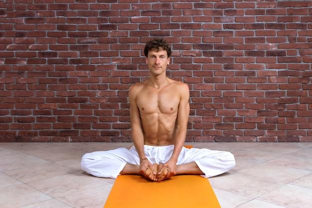 Desportivo homem praticando hatha yoga em um estúdio