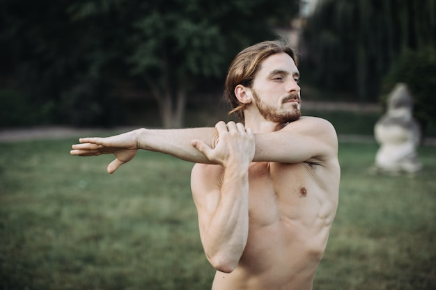 Desportivo homem praticando ioga ao ar livre