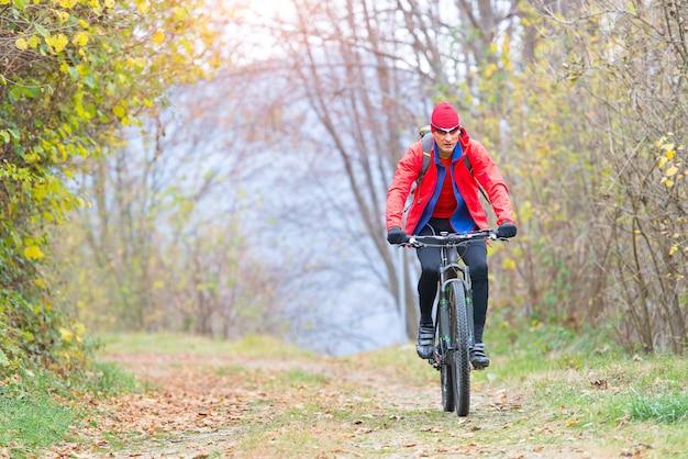 Desportivo homem relaxa pedalando uma bicicleta de montanha na floresta