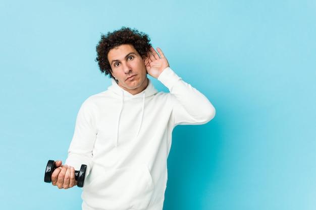 Desportivo homem segurando um dumbbel tentando ouvir uma fofoca.
