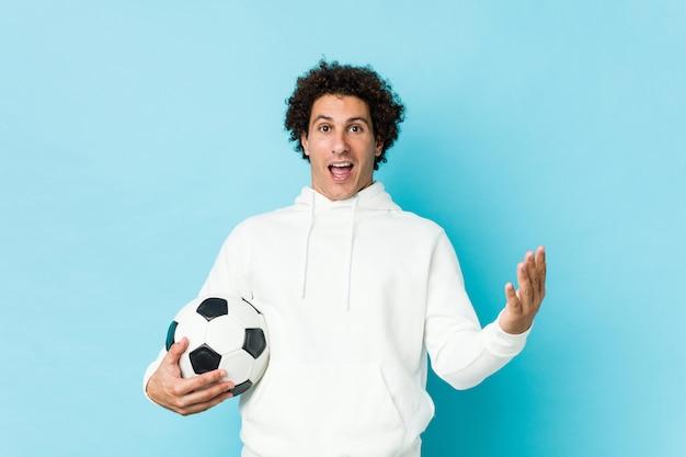 Desportivo homem segurando uma bola de futebol comemorando uma vitória ou sucesso