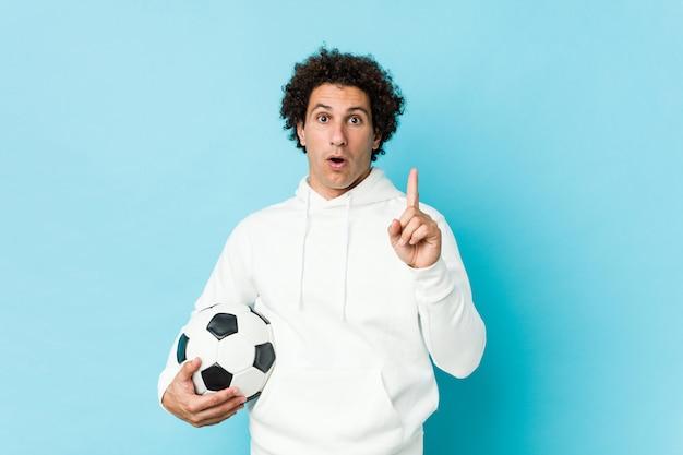 Desportivo homem segurando uma bola de futebol, tendo uma ótima idéia, conceito de criatividade.