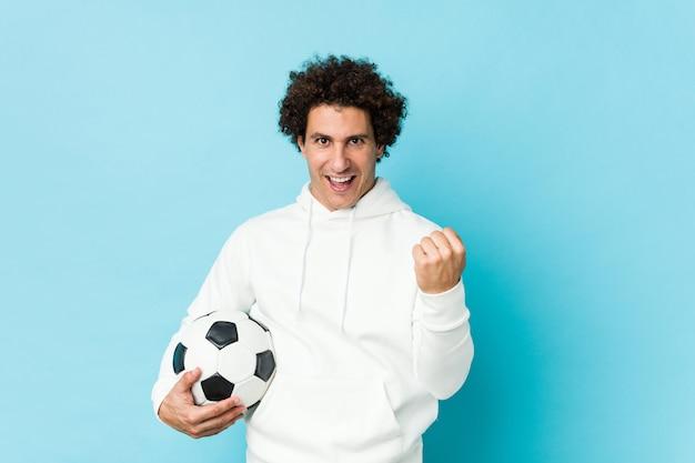 Desportivo homem segurando uma bola de futebol torcendo despreocupado e animado. conceito de vitória