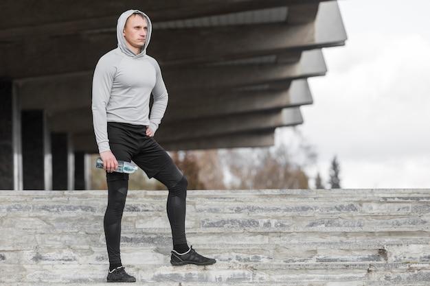 Desportivo homem sentado na escada e posando de moda