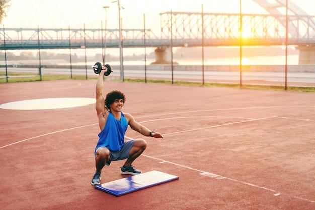 Desportivo homem vestido com roupas esportivas e cabelos cacheados fazendo agachamentos, mantendo o haltere na mão. corte no exterior da manhã.