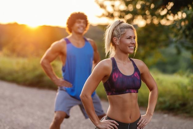 Desportivo par caucasiano fazendo exercícios de fitness na estrada rural no dia ensolarado de verão. foco seletivo na mulher.