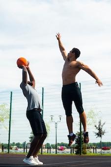 Desportivos homens pulando na quadra de basquete