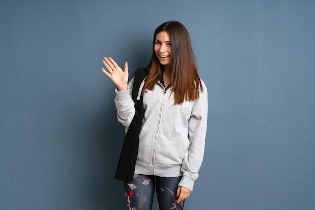 Desporto jovem mulher saudando com mão com expressão feliz