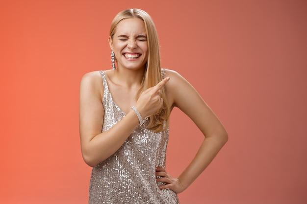 Despreocupada alegre loira atraente mulher se divertindo, brincando, rir roupa de namorado hilário fechar os olhos rindo sorrindo amplamente apontando o canto superior direito atrás de fundo vermelho em pé.