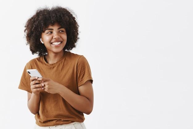 Despreocupada, amigável e criativa, elegante adolescente afro-americana com camiseta marrom, virando à direita com largo sorriso satisfeito, usando fones de ouvido sem fio e segurando um smartphone