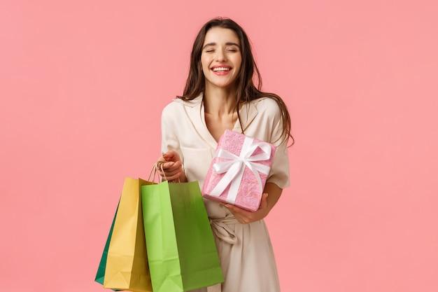 Despreocupada e encantada viciada em compras feminina, garota recebeu muitos presentes, segurando a sacola de compras e o presente embrulhado fofo, fechar os olhos e sorrir sonhadora curtindo a festa de aniversário, parede rosa em pé