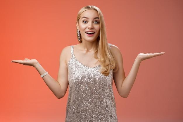 Despreocupada e fascinada jovem loira de 20 anos em prata brilhante vestido de festa de noite levantando as mãos para os lados pesando encolher os ombros sorrindo divertido pesquisar a escolha certa, decidindo o que fazer fundo vermelho.
