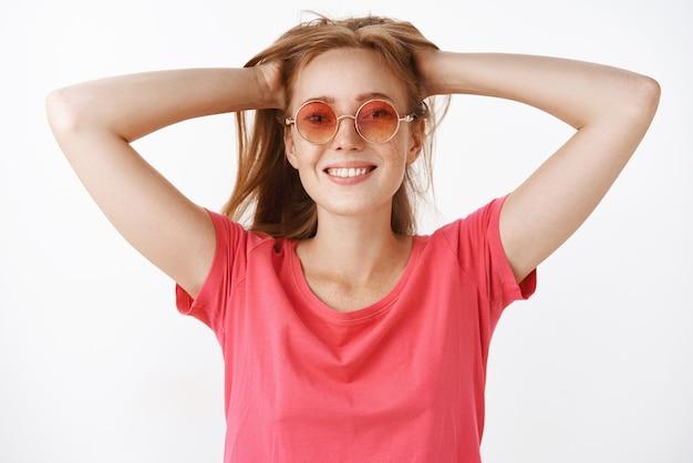 Despreocupada e fofa mulher ruiva com sardas e lindo sorriso largo segurando o cabelo para trás com as duas mãos olhando satisfeita e despreocupada relaxando