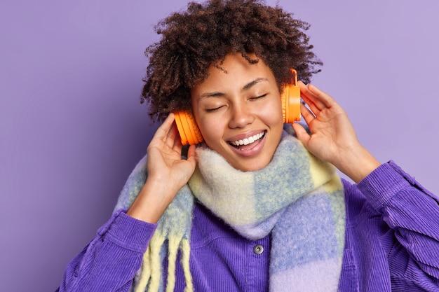 Despreocupada e otimista adolescente afro-americana com sorrisos largos, mantém as mãos nos fones de ouvido estéreo, ouve música, mantém os olhos fechados, usa um lenço quente no pescoço