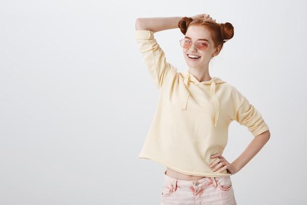 Despreocupada e sorridente ruiva de óculos escuros aproveitando o verão