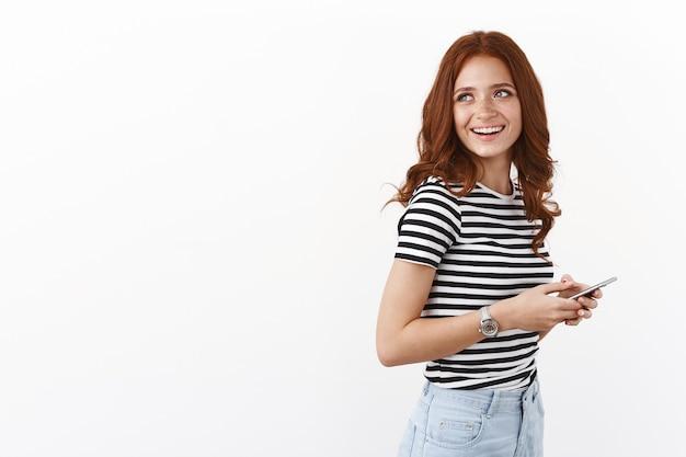 Despreocupada e terna menina europeia com penteado ruivo cacheado, perfil em pé usando smartphone, vire à esquerda e sorrindo alegremente, conversando com um amigo que está por perto, recontando meme engraçado nas redes sociais