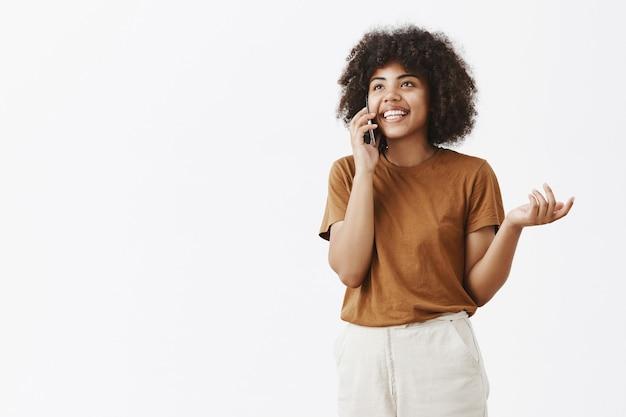 Despreocupada, feliz, bonita e emotiva garota afro-americana com cabelo encaracolado olhando para cima, gesticulando e sorrindo ao usar o celular