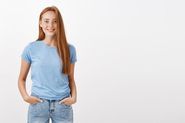 Despreocupada, fofa e tímida jovem ruiva feliz com sardas sorrindo alegremente de mãos dadas nos bolsos, em pose casual comum amigável e alegre